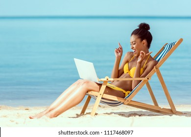 smiling african american woman gesturing by fingers and communicating by laptop while sitting on deck chair on sandy beach