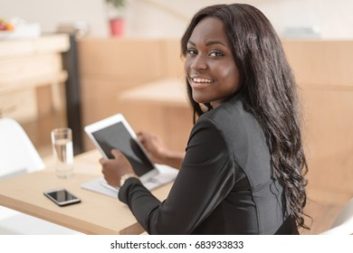 smiling african american woman holding digital tablet with blank screen while sitting in cafe