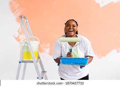 Smiling african american woman painting interior wall of home. Renovation, repair and redecoration concept.