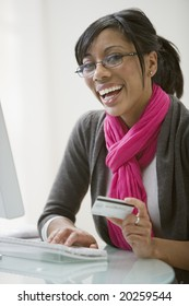 Smiling African American woman shopping on-line with credit card and computer