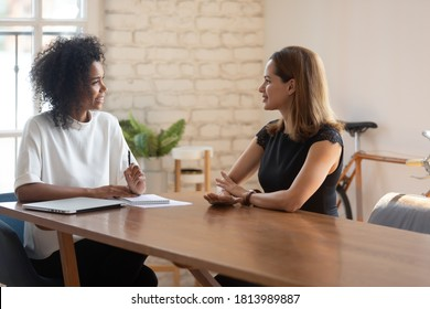 Smiling African American young businesswoman talk negotiate with female Caucasian job candidate at office meeting, happy biracial boss discuss ideas with business partner or employee at interview