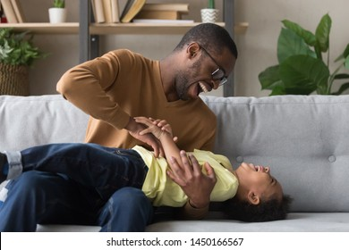 Smiling african American young dad have fun playing with cute little preschooler son on couch at home, excited happy black father entertain engaged in funny game tickle laugh small biracial boy kid