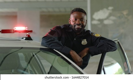 Smiling african american young man cops stand near patrol car look at camera enforcement happy officer police uniform auto safety security communication control policeman close up slow motion