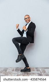 Smiling african american young man standing and celebrating success