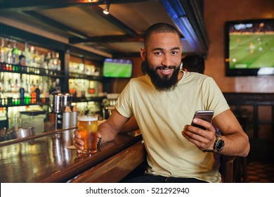 Smiling african american young man drinking beer and using cell phone in pub