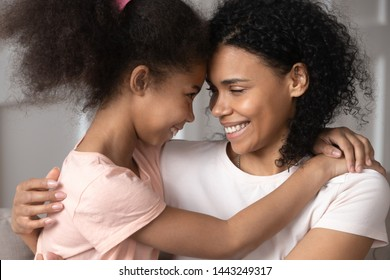 Smiling african American young mom and little daughter hug look in eyes feel happy to reconcile, loving black mother and small preschooler biracial girl kid have close tender moment together
