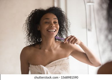 Smiling african American young woman in towel look in mirror brush teeth with toothbrush in home bathroom, happy biracial female do morning daily routine, oral treatment, personal hygiene concept