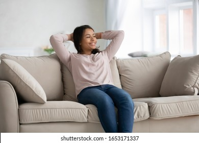 Smiling African American young woman sit relax on couch in living room look in window distance dreaming, happy biracial female rest on cozy sofa at home thinking pondering or visualizing