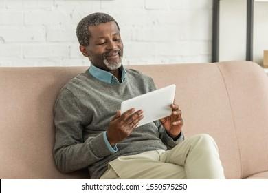 smiling african anerican man using laptop while sitting on sofa