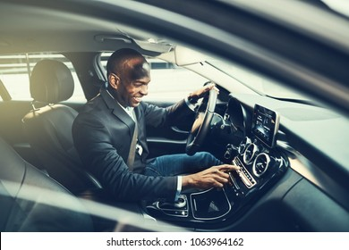 Smiling African businessman changing stations on his car radio while driving through the city during his morning commute to work