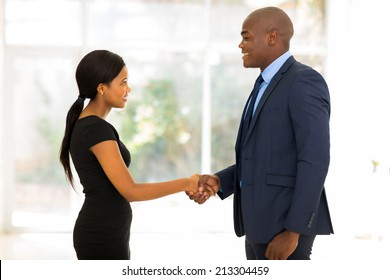smiling african businessman handshaking with young businesswoman in office