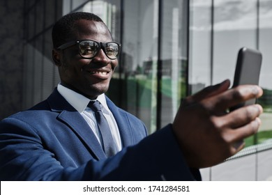 Smiling african businessman using smart phone outdoor