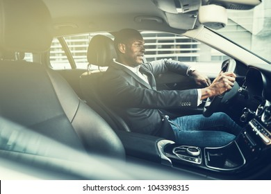 Smiling African businessman wearing a blazer driving his car during his morning commute to work through the city