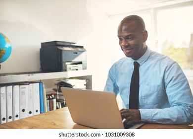 Smiling African businessman wearing a shirt and tie sitting at a desk working online with a laptop in his home office