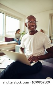 Smiling African businessman working at his office desk using on a laptop with colleagues sitting in the background