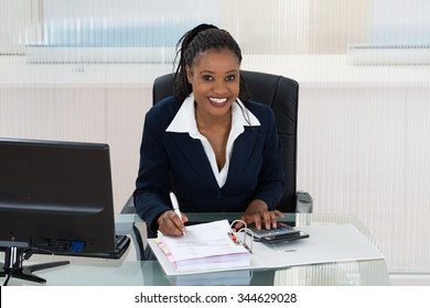 Smiling African Businesswoman Calculating Bills At Office Desk