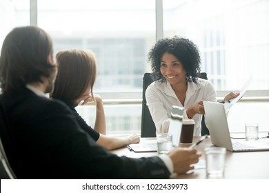 Smiling african businesswoman discussing positive work result with caucasian partners, friendly black executive manager talking to colleagues about corporate report sharing good news at team meeting