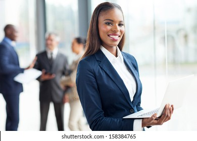 smiling african businesswoman with laptop computer