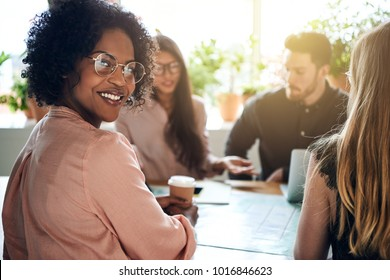 Smiling African businesswoman sitting at an office table looking over her shoulder with colleagues working in the background