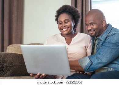 Smiling African couple browsing online with a laptop while sitting and relaxing together on their living room sofa at home
