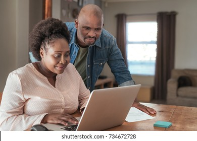 Smiling African couple doing their online banking and paying bills with a laptop at their kitchen table at home