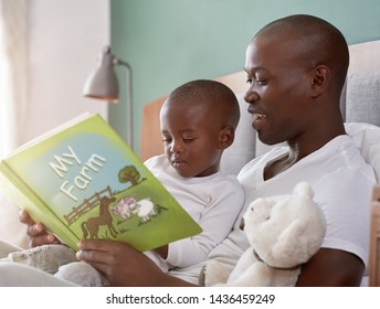 Smiling african dad reading to his child in bed, father and son bonding family time