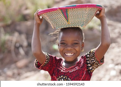 Smiling African Ethnic Girl Outdoors with Food Basket, poverty symbol