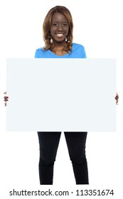 Smiling african female model holding billboard over white background