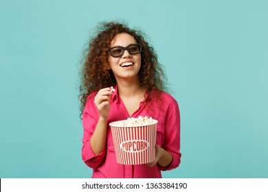 Smiling african girl in 3d imax glasses watching movie film and holding popcorn isolated on blue turquoise wall background in studio. People emotions in cinema, lifestyle concept. Mock up copy space