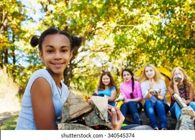 Smiling African girl holding kindling wood