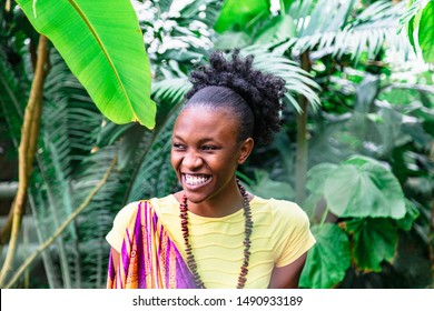 Smiling african girl on background of green plants