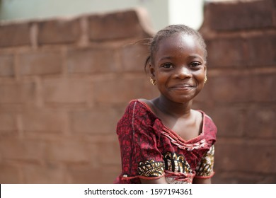 Smiling African Girl With a Wet Face After Having Taken A Sip From The Water Borehole