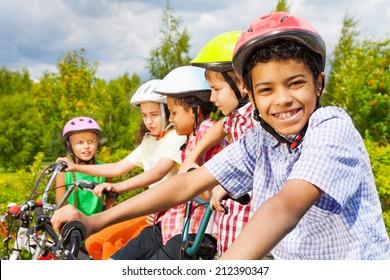 Smiling African guy in helmet with friends behind
