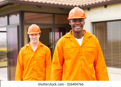 smiling african handyman standing in front of colleague before house renovation