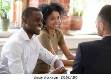 Smiling african hr managers recruiters listening to male applicant at recruiting job interview, happy black couple consulting realtor insurer bank worker making offer to clients at meeting in office
