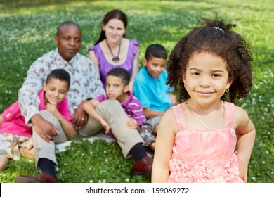 Smiling african little girl stands in foreground, her family of five sits behind on green lawn not in focus