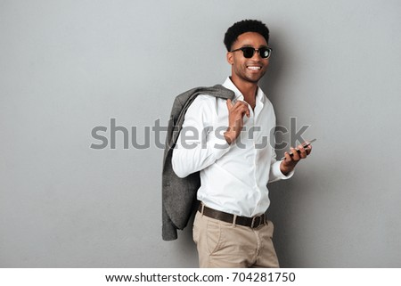90812cc9cee2 Smiling african man in sunglasses holding jacket over shoulder and using  mobile phone isolated over gray