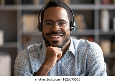 Smiling african professional telemarketer call center operator wear wireless headset look at camera, afro american business man customer technical customer support service closeup headshot portrait