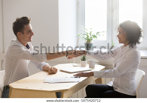 Smiling african realtor and satisfied caucasian client shaking hands making real estate deal, happy white customer handshaking black agent making mortgage loan investment, buying new house concept