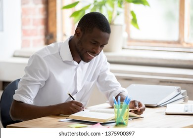 Smiling african student do easy exercise homework assignment preparing for test sitting at desk feels satisfied, hold pen makes notes reading textbook chapter, interesting study self education concept