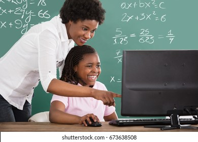 Smiling African Teacher Teaching Her Student On Computer In Class