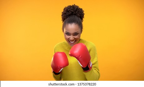 Smiling african teenager in boxing gloves imitating fight, having fun, victory