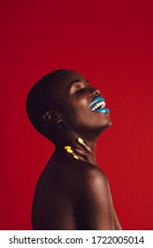Smiling african woman with colorful makeup. Closeup of a african female model with vibrant makeup on red background.