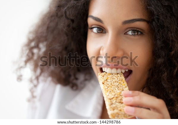 Smiling African woman eating a heathy cereal snack bar.