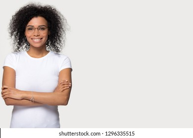 Smiling african woman in glasses with arms folded standing isolated on white grey blank background with copy space for advertisement aside, happy confident black lady student look at camera, portrait