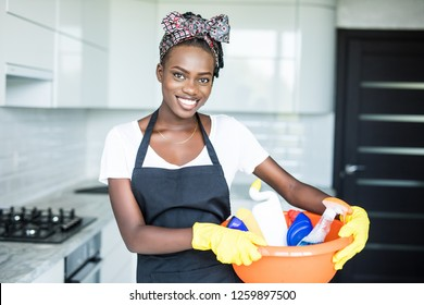 Smiling African Woman Holding Basket With Cleaning Equipment