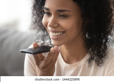 Smiling african woman holding phone speak activate virtual digital voice assistant on smartphone, happy black girl ask internet assistance service make call, easy mobile ai technology concept