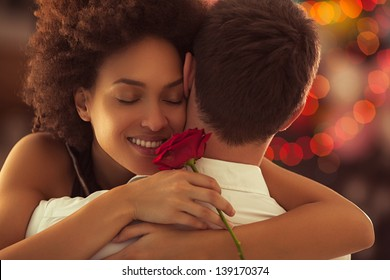 Smiling African woman hugging her boyfriend and holding the rose she got for Valentine's Day.
