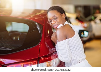 Smiling african woman hugging a red car at new car showroom