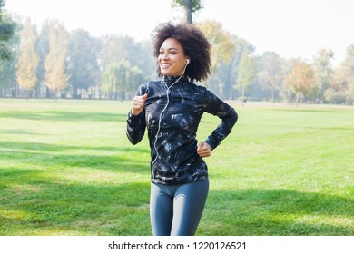 Smiling African woman jogging and listening at the music in nature on summer day